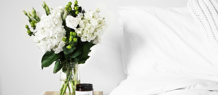 Flowers next to white bed